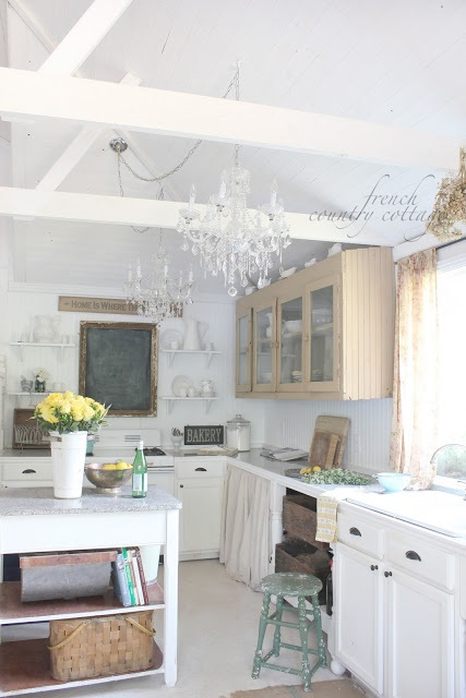 Two crystal chandeliers hang over a kitchen area.