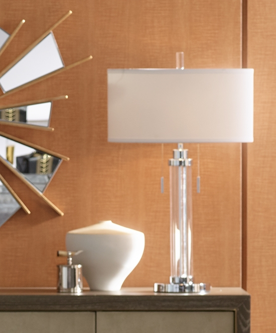 A column style table lamp among white and mirrored decor.