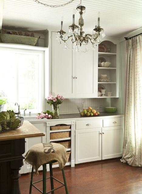 A country style kitchen with a vintage-look chandelier.