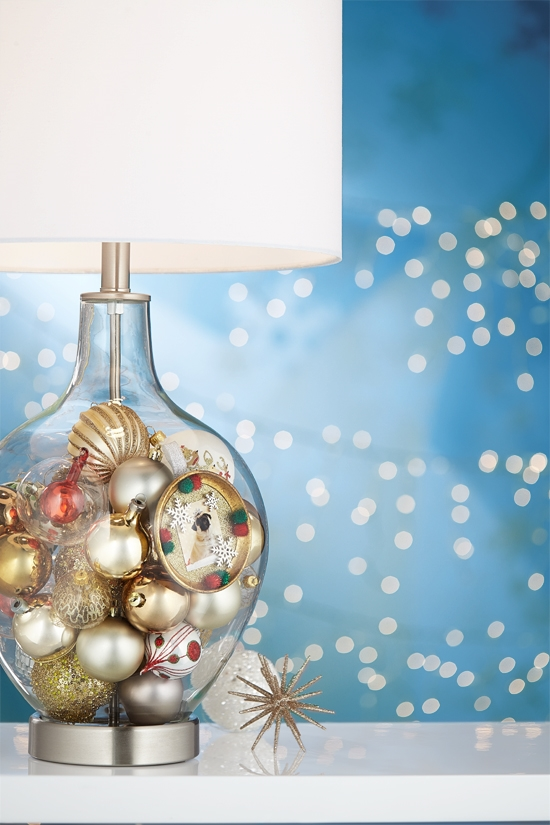 A clear glass table lamp filled with ornaments.
