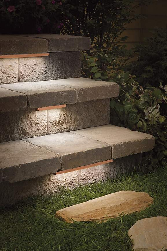Low-profile contemporary stair lighting under treads of outdoor stone steps.