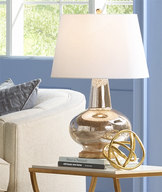 A table lamp with a mercury glass finish base.