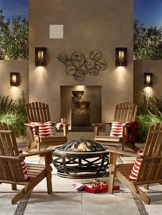 Outdoor nighttime scene with four acacia wood Adirondack chairs with red-and-white patterned pillows and an outdoor fire pit.