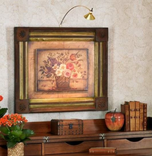 A picture light mounted over a framed art piece.