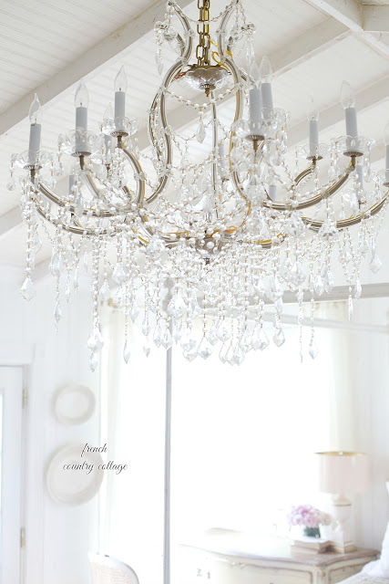 A large crystal chandelier hangs over a white themed room.