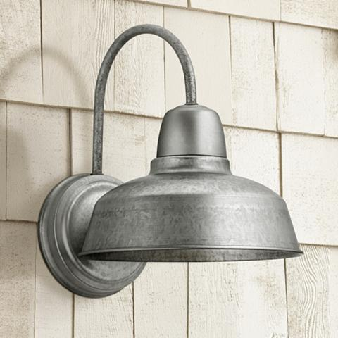 A galvanized steel finish barn light in a rustic setting.