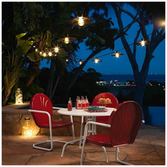 A picture of an outdoor table illuminated by party string lights