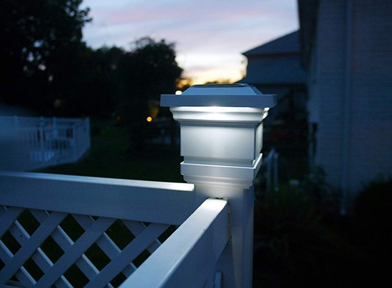 White solar LED post cap on a wood banister.