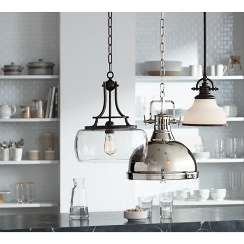 Three industrial-style pendant lights in a clean, contemporary kitchen setting.
