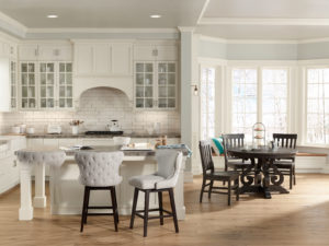 A beautiful, bright transitional kitchen, illuminated by an island pendant and recessed lighting.