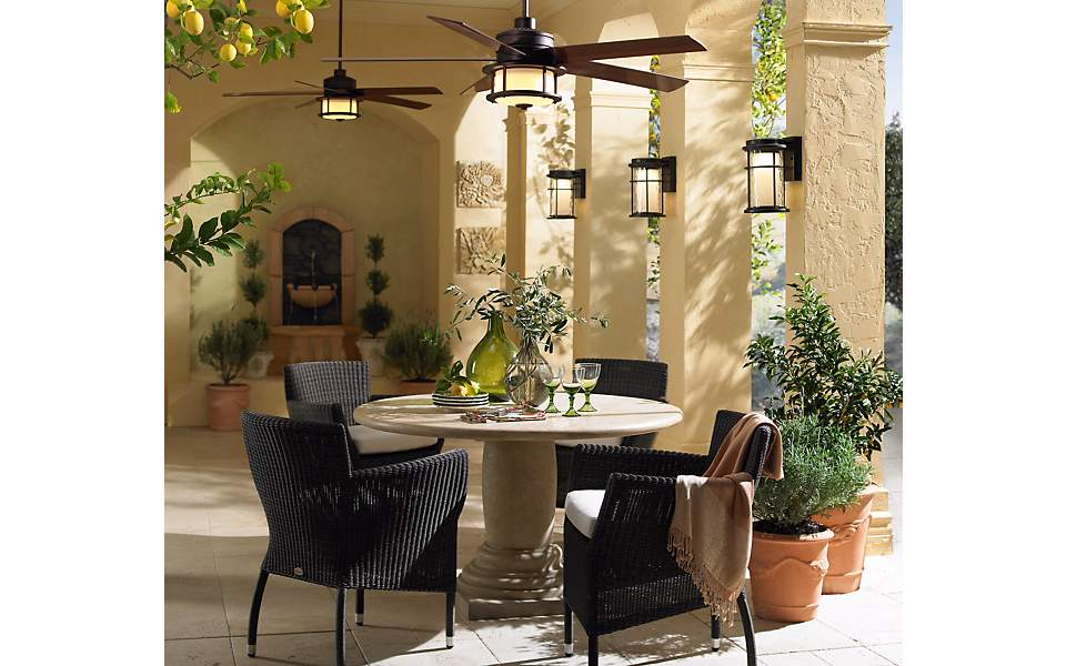 A patio scene with outdoor wall lights and ceiling fans with lights.
