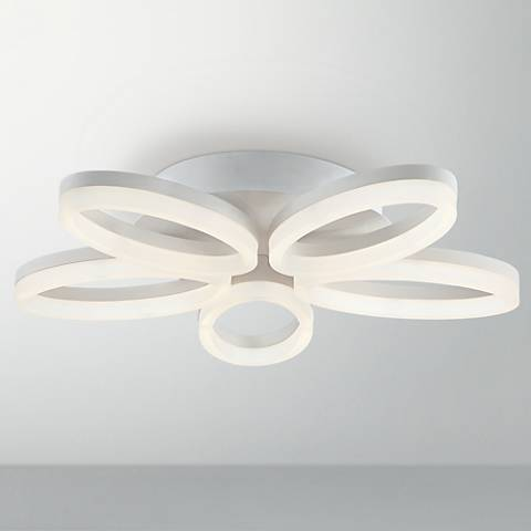 A contemporary white close to ceiling light in a flower shape.