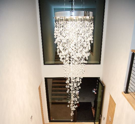 A sparkling crystal chandelier hanging in an entryway.